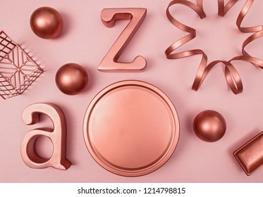 Decorative metal objects on pastel pink background. Copper, rose gold color.