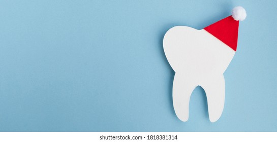 Decorative model tooth in a red Santa Claus hat on light blue background. Christmas and New Year concept. Creative medical winter postcard for dentistry. Top view, banner, copy space