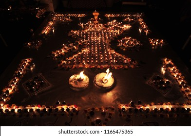 Decorative oil or wax burning traditional Diwali Diya or lamps arranged with shiva linga in a shape of symbolic Hindu lord Shiva's trishul (trident) and damru (instrument).