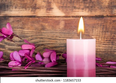 Decorative Ombre purple aromatic candle with flame and branches with flower on wooden background. . Beauty spa treatment and relax concept. Close up, selective focus
