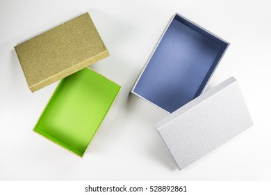Decorative Open Small Silver Box with Blue Inside and Gold Box with Green Inside on White Background. Top View.