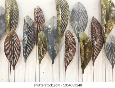 Decorative ornament with leaf made from metal on white background.