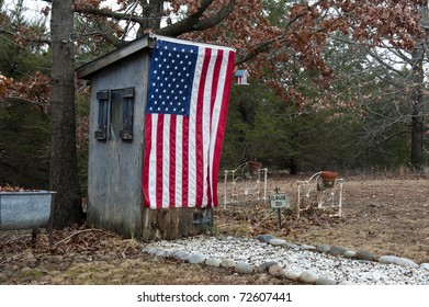 Decorative Outhouse draped in an American Flag