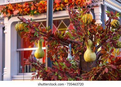 Decorative and painted pumpkins on an artificial tree with vinous leaves. Colorful autumn in Moscow city, Russia.
