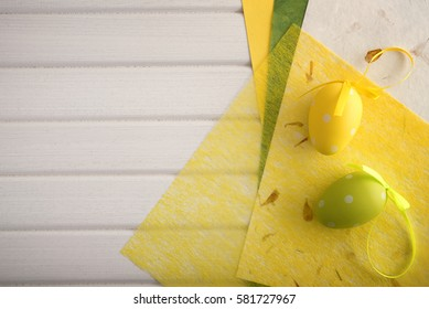 Decorative paper and easter eggs on wooden table.