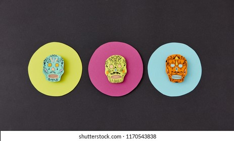 Decorative pattern from round frames with creative handmade skulls on a black paper background. Flat lay. Calaveras simbol of the Mexican holiday of Calaca. Flat lay
