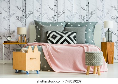 Decorative pillow with geometric pattern in feminine bedroom interior with wooden accessories
