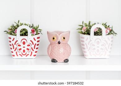 Decorative pink owl moneybox and trinket on white shelf