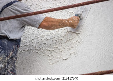 Decorative plaster applied on the surface by a steel trowel. White cement based decorative top coat plaster resistant on outside whether conditions. Selective focus.