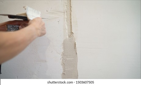 Decorative plaster coating. Man does ragged texture on the wall using a spatula. plaster application on the wall