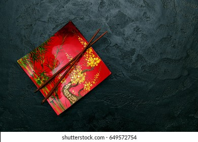 Decorative plate in Asian style and chopsticks on the black background. Top view. Space for a text.