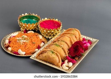 Decorative Plates And Tray With Delicious Gujia Or Gujiya Mithai Jalebi Ghewar Dry Fruits And Colorful Gulal Abeer Or Abir For Happy Holi Celebration Isolated On Black Background
