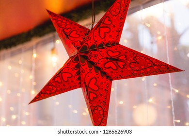 Decorative red and black star ornament hanging in a window with Christmas lights and buildings in background.