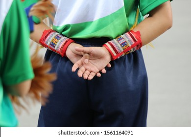 Decorative red fashion wristbands with an oriental pattern covering the lower forearms of a girl