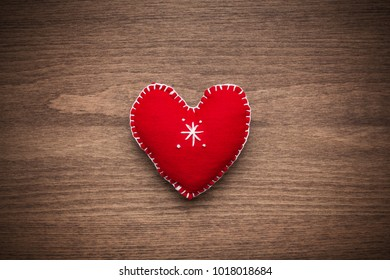 Decorative red heart on a wooden background