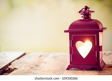 Декоративный красный металлический фонарь с вырезом сердца, освещенный светящейся свечей с копипространства для Святого Валентина или Рождества