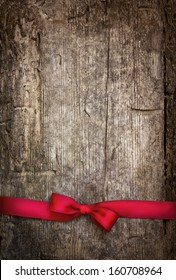 Decorative red ribbon and bow over wooden background/holidays background with copyspace