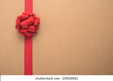 Decorative red ribbon and bow over corrugated cardboard