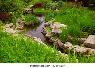 Decorative rocks near a small pond in a garden