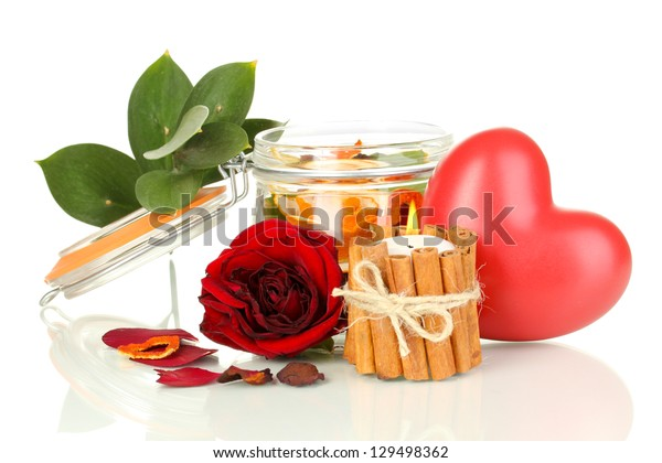 Decorative rose from dry orange peel in glass vase and burning candle isolated on white