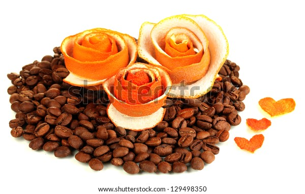 Decorative roses from dry orange peel on coffee beans heap