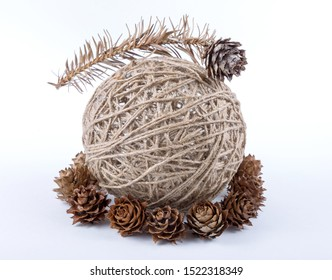 Decorative round clew of twine on a white background with pine cones and a sprig close-up