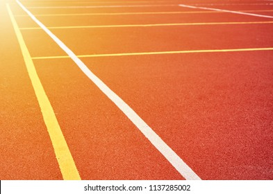 Decorative rubberized Jogging coating at the street stadium in outdoor with white line. Sport Background with sunlight effect.