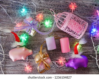 Decorative seasonal composition of Christmas toy piglets in Santa's red hats, festive illumination, candles, boxes with balls, lanterns on a wooden table, pink color, the year of the pig, Christmas, t