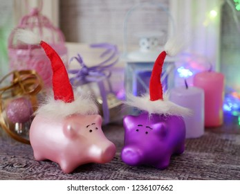 Decorative seasonal composition of Christmas toy piglets in Santa's red hats, festive illumination, candles, boxes with balls, lanterns on a wooden table, pink color, the year of the pig, Christmas