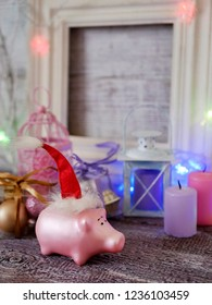 Decorative seasonal composition of a New Year's pig toy in a red Santa hat, festive illumination, candles, boxes with balls, lanterns on a wooden table, pink color, the year of the pig, Christmas