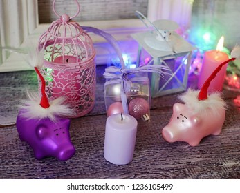 Decorative seasonal composition of toy New Year piglets in red Santa hats, festive illumination, lit candles, boxes with balls, lanterns on a wooden table, pink color, the year of the pig, Christmas