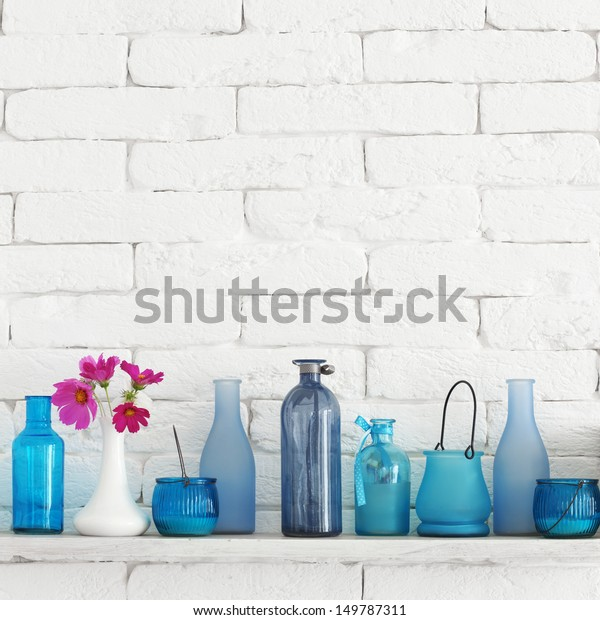 Decorative shelf on white brick wall with blue bottles on it