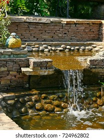 Decorative small waterfall in a city Park.