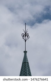 Decorative spire against a cloudy sky