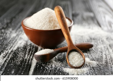 Decorative spoons and bowl with white sugar on black wooden background