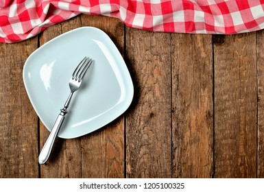 Decorative square plate, fork, and red checkered tablecloth on top side on old vintage wooden table background - view from above