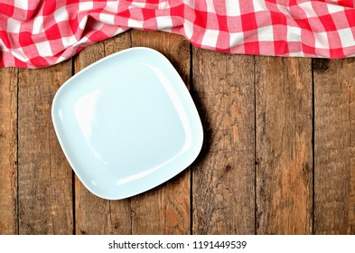 Decorative square plate, and red checkered tablecloth on top side on old vintage wooden table background - view from above