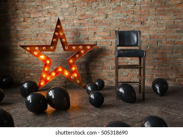Decorative star with lamps and black balloons on the floor. Modern grungy interior. Space for the Halloween.