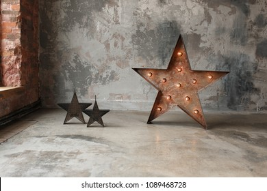 Decorative star with lamps on a background of concrete wall. Modern grungy loft interior