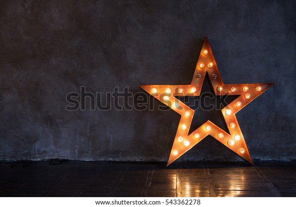 Decorative star with lamps on a background of wall. Modern grungy interior