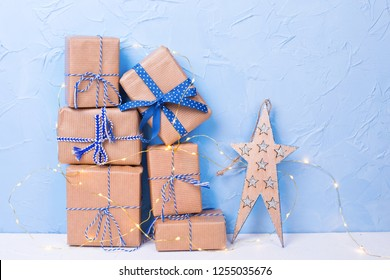 Decorative star and stack or pile of wrapped boxes with presents and fairy lights  on white textured background against blue wall. Selective focus. Place for text. Holiday shopping concept.