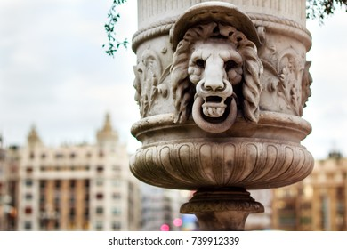 Decorative stone vase in the old town od San Sebastian, Spain. Vase is ornated with lion's head. Town buildings are defocused on the background.