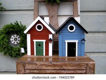 Decorative street composition in Swedish style. Bird houses in the old chair against the background of a wooden wall. Close up. Selective focus.