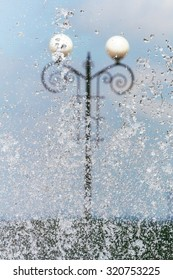 Decorative street lamp through the city fountain jet and water drops