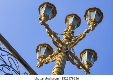 Decorative street light in retro style painted in gold color
