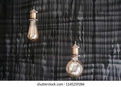 Decorative style antique edison light bulbs on the dark gray wall background. Loft interior details, decor in restaurant on wedding.