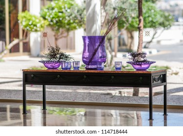 decorative table with purple vases against the window