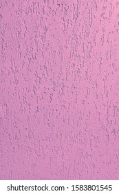 Decorative textured wall stucco bark beetle pink grain. Rough pink painted surface