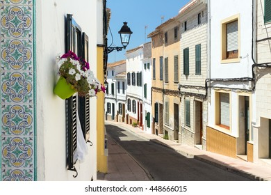 Decorative tiles and flowers at Alaior, Menorca - focus on houses. Small houses and a nice fassade decoration in a small city alley.