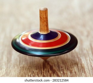 Decorative top spinning on wooden surface